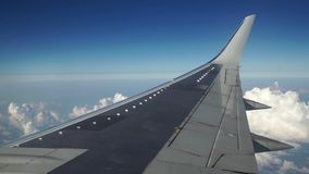 Airplane is flying in the blue sky through the white clouds. View of the airplane wing from the window. Traveling, transportation concept stock video