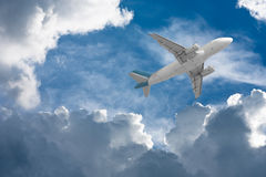 Airplane flying through clouds. In sky towards the sun Stock Photos