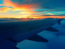 Airplane flying clouds sunset. Airplane flying above the clouds stock photo