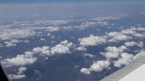 Airplane flying into the clouds. view through an airplane window. traveling b stock video footage