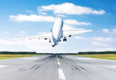 Airplane flying departure take off on a runway airport good weather with a blue sky clouds on a runway. Back view. Royalty Free Stock Photo