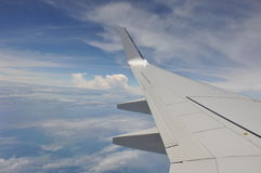Airplane flying down. against the sky. Large aircraft is going for landing. Against cloudy sky Stock Photos