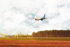 Airplane flying down near field and forest Royalty Free Stock Image