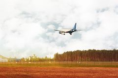 Airplane flying down near field and forest Stock Image