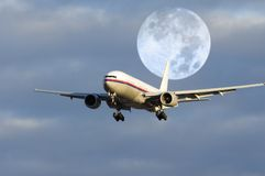 Airplane flying in front of moon. Airplane and moon in early evening Royalty Free Stock Photos