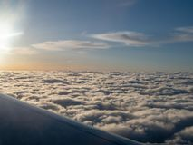 Airplane flying high above stratocumulus clouds during morning s. Airplane flying high above stratocumulus clouds during the morning sunrise stock photo