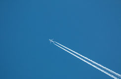 Airplane flying at high altitude. Leaving its white wake over blue sky royalty free stock photo