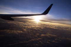 Airplane flying high in the blue sky Stock Photos
