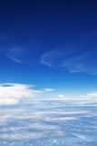 Airplane flying in mid air above clouds. Clear sky background Stock Images