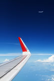 Airplane flying in mid air above clouds. Clear sky background Stock Photos