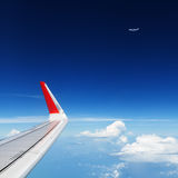 Airplane flying in mid air above clouds. Clear sky background Stock Image