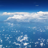 Airplane flying in mid air above clouds. Clear sky background Royalty Free Stock Images
