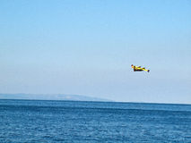 Airplane flying near blue sea Stock Photography