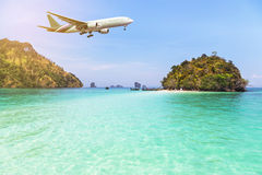 Airplane flying over above tropical island in the sea. Stock Photo