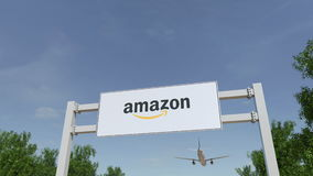 Airplane flying over advertising billboard with Amazon.com logo. Editorial 3D rendering royalty free stock photos