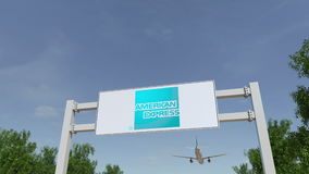 Airplane flying over advertising billboard with American Express logo. Editorial 3D rendering Royalty Free Stock Photos