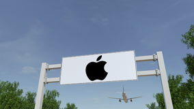 Airplane flying over advertising billboard with Apple Inc. logo. Modern office building entrance. Editorial 3D rendering. Airplane flying over advertising stock images