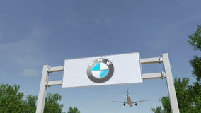 Airplane flying over advertising billboard with BMW logo. Editorial 3D rendering Royalty Free Stock Image