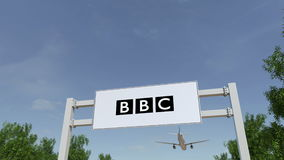 Airplane flying over advertising billboard with British Broadcasting Corporation BBC logo. Editorial 3D rendering 4K. Animation stock video