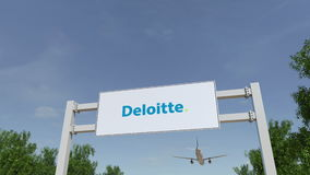 Airplane flying over advertising billboard with Deloitte logo. Editorial 3D rendering Royalty Free Stock Photo