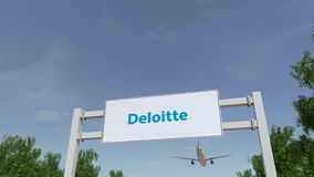 Airplane flying over advertising billboard with Deloitte logo. Editorial 3D rendering 4K clip stock video