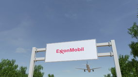 Airplane flying over advertising billboard with ExxonMobil logo. Editorial 3D rendering 4K clip vector illustration
