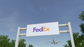 Airplane flying over advertising billboard with FedEx logo. Editorial 3D rendering Stock Photos