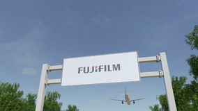 Airplane flying over advertising billboard with Fujifilm logo. Editorial 3D rendering Stock Images