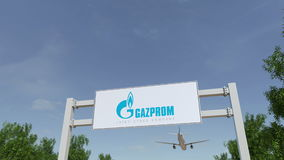 Airplane flying over advertising billboard with Gazprom logo. Editorial 3D rendering 4K clip stock illustration