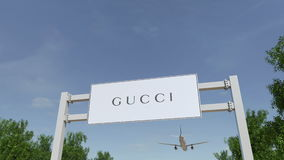 Airplane flying over advertising billboard with Gucci logo. Editorial 3D rendering. Airplane flying over advertising billboard with Gucci logo. Editorial 3D stock photography