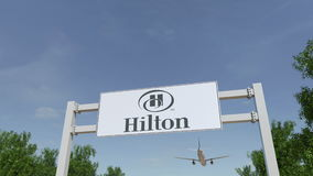 Airplane flying over advertising billboard with Hilton Hotels Resorts logo. Editorial 3D rendering. Airplane flying over advertising billboard with Hilton Hotels Stock Image