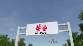 Airplane flying over advertising billboard with Huawei logo. Editorial 3D rendering Stock Image