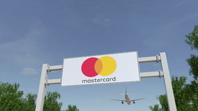 Airplane flying over advertising billboard with MasterCard logo. Editorial 3D rendering Royalty Free Stock Image
