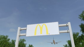 Airplane flying over advertising billboard with McDonald`s logo. Editorial 3D rendering Stock Photo