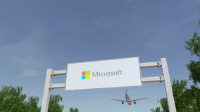 Airplane flying over advertising billboard with Microsoft logo. Editorial 3D rendering 4K clip