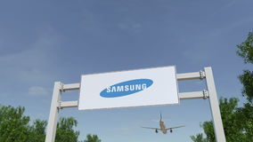 Airplane flying over advertising billboard with Samsung logo. Editorial 3D rendering Stock Photography
