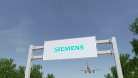 Airplane flying over advertising billboard with Siemens logo. Editorial 3D rendering Royalty Free Stock Photo
