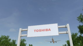 Airplane flying over advertising billboard with Toshiba Corporation logo. Editorial 3D rendering 4K clip royalty free illustration