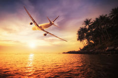 Airplane flying over amazing tropical sunset landscape Stock Photos