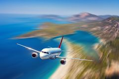Airplane is flying over blue sea and mountains at sunset stock photos