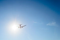 Airplane flying over the blue sky and sun rays background Royalty Free Stock Photo
