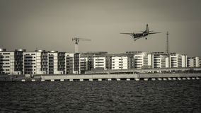 Airplane flying over buildings and water. Prepare for landing. Stock Images