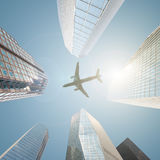 An airplane flying over a business center filled with skyscrapers Stock Image
