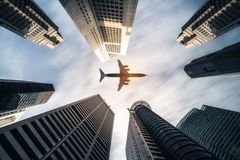 Airplane flying over city business buildings, high-rise skyscrapers. Airplane flying over city buildings, high-rise business skyscrapers. Tourism, transport stock photography