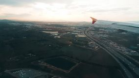 Airplane flying over the city, view from the window. Airplane flying over the city in the cloudy sky, view from the window stock video footage