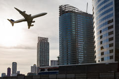 Airplane flying over city with sky train Stock Images