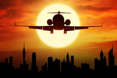 Airplane flying over the city at sunset time. Silhouette of aircraft flying over a town with sunset on the background Stock Photography