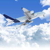 Airplane flying over the clouds. Big Jet airplane flying over a clear cloudscape seen from the bottom at takeoff, clipping path on the plane for easy isolation Royalty Free Stock Image