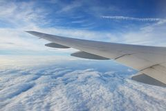 Airplane Flying Over Clouds. In blue skies royalty free stock image