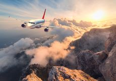 Landscape with white passenger airplane, mountains, sea and orange sky. Airplane is flying over clouds at sunset. Landscape with white passenger airplane Stock Photo